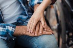 конец вверх Несколько invalids на кресло-колясках встречали в парке Человек и женщина сидят держащ руки Стоковые Изображения