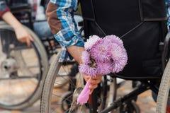конец вверх Несколько invalids на кресло-колясках встречали в парке Человек держит букет цветков Стоковое Изображение RF