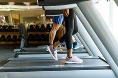 Конец-вверх ног женщины и человека подходящих бежать на третбане Стоковая Фотография