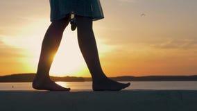 Конец-Вверх ног женщин на пляже в лучах фликера захода солнца видеоматериал