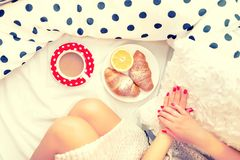 Конец-вверх ног и завтрака женщины в кровати с круассанами, кофе и апельсиновым соком Стоковые Изображения
