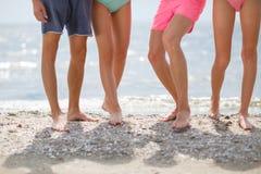 Конец-вверх ног на предпосылке моря Группа в составе sporty подростки идя около голубого океана портрет 2 пеликанов приятельства  Стоковое Фото