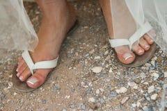 Конец вверх ног невест в темповых сальто сальто на пляже с деланными маникюр ногтями стоковое фото