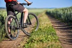Конец-вверх ног человека велосипедиста с горным велосипедом на следе поля в сельской местности Стоковое Изображение