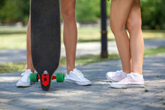 Конец-вверх ног ` teenages в белых тапках отдыхая после весьма смешной езды на деревянном скейтборде longboard скопируйте космос Стоковое фото RF