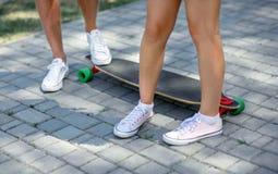 Конец-вверх ног ` teenages в белых тапках отдыхая после весьма смешной езды на деревянном скейтборде longboard скопируйте космос Стоковая Фотография RF