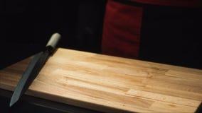 Конец-вверх ножа на разделочной доске Деревянная доска и нож готовые для того чтобы сварить на темной предпосылке Детали для реза стоковое фото rf