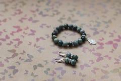 Конец-вверх ожерелья и серег зеленых яшмы и серебра на предпосылке с пестроткаными бабочками стоковые изображения