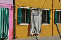 Конец-вверх окон на красочных стенах и двери с тканью в Burano Стоковое Фото