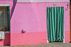 Конец-вверх окон на красочных стенах и двери с тканью в Burano Стоковое Изображение