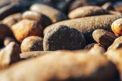 Конец-вверх округленных камней на морском побережье в лучах солнца захода солнца стоковое фото rf