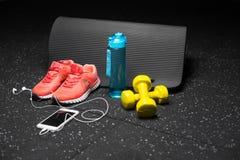 Конец-вверх оранжевых ботинок спорта, желтых гантелей, циновки pilates, голубой бутылки, и телефона с наушниками на черноте Стоковые Фото