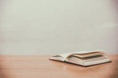 Конец вверх открытой книги на столе с винтажной предпосылкой нерезкости фильтра Стоковые Изображения RF