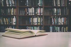 Конец вверх открытой книги на столе с винтажной предпосылкой нерезкости фильтра Стоковые Фотографии RF