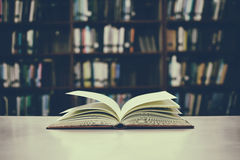 Конец вверх открытой книги на столе с винтажной предпосылкой нерезкости фильтра Стоковое Изображение