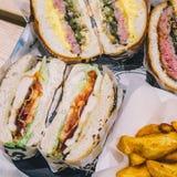 Конец-вверх отрезал бургеры мяса и французский картофель фри на подносе в кафе стоковая фотография rf