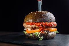 Конец-вверх очень вкусного свежего домашнего сделанного бургера с салатом, луком и томатом Большое количество томатного соуса Стоковое Изображение RF