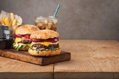 Конец-вверх очень вкусного свежего домашнего сделанного бургера с салатом, сыром, луком и томатом на деревенской деревянной планк Стоковые Изображения