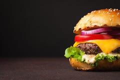 Конец-вверх очень вкусного свежего домашнего сделанного бургера с салатом, сыром, луком и томатом на темной предпосылке с космосо Стоковое Фото