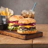 Конец-вверх очень вкусного свежего домашнего сделанного бургера с салатом, сыром, луком и томатом на деревенской деревянной планк Стоковая Фотография