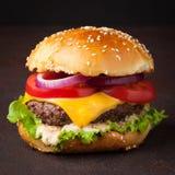 Конец-вверх очень вкусного свежего домашнего сделанного бургера с салатом, сыром, луком и томатом на темной предпосылке фаст-фуд  Стоковые Изображения