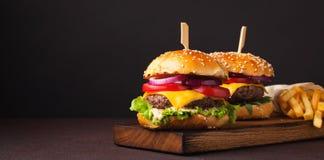 Конец-вверх очень вкусного свежего домашнего сделанного бургера с салатом, сыром, луком и томатом на темной предпосылке с космосо Стоковые Фотографии RF