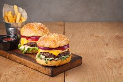 Конец-вверх очень вкусного свежего домашнего сделанного бургера с салатом, сыром, луком и томатом на деревенской деревянной доске Стоковые Фотографии RF