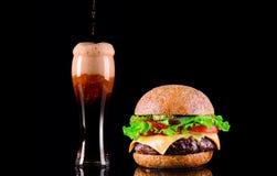 Конец-вверх очень вкусного свежего домашнего сделанного бургера с салатом, сыр, лук, томат и кола выпивают или темное пиво с льдо Стоковые Изображения RF