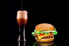 Конец-вверх очень вкусного свежего домашнего сделанного бургера с салатом, сыр, лук, томат и кола выпивают или темное пиво с льдо Стоковая Фотография RF