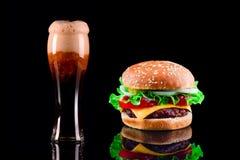 Конец-вверх очень вкусного свежего домашнего сделанного бургера с салатом, сыр, лук, томат и кола выпивают или темное пиво с льдо Стоковые Фото