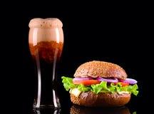 Конец-вверх очень вкусного свежего домашнего сделанного бургера с салатом, сыр, лук, томат и кола выпивают или темное пиво с льдо Стоковое Изображение