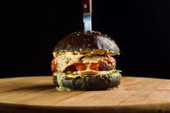 Конец-вверх очень вкусного свежего домашнего сделанного бургера говядины с салатом, сыром, луком и томатом Висит угол сыра Стоковые Изображения