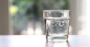 Конец вверх очистил свежую воду питья от бутылки на таблице i Стоковые Изображения RF