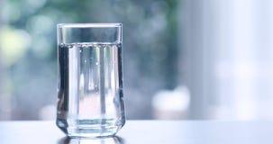 Конец вверх очистил свежую воду питья от бутылки на таблице внутри Стоковое Изображение