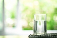 Конец вверх очистил свежую воду питья от бутылки на таблице внутри Стоковые Фото