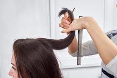 Конец-вверх парикмахера режа волосы женщины стоковое изображение rf