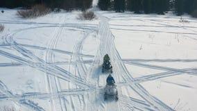 Конец-вверх 2 парней идя на снегоходы на снежном следе около хвойных деревьев footage Участвовать в гонке зимы стоковое изображение rf