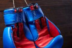Конец-вверх пар голубых и красных перчаток бокса вися в деревянной стене Стоковые Фотографии RF
