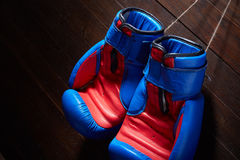 Конец-вверх пар голубых и красных перчаток бокса вися в деревянной стене Стоковое Фото
