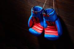 Конец-вверх пар голубых и красных перчаток бокса вися в деревянной стене Стоковые Фото