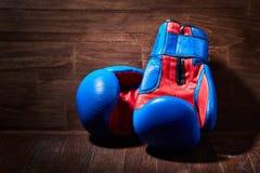 Конец-вверх пар красных и голубых перчаток бокса на деревянной планке Стоковые Фото