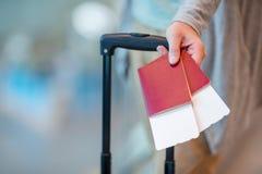 Конец-вверх пасспортов и посадочного талона в мужских руках на авиапорте Стоковая Фотография