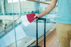 Конец-вверх пасспортов и посадочного талона в мужских руках на авиапорте Стоковое Изображение