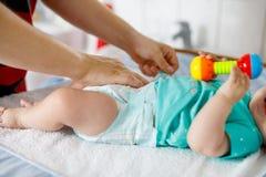 Конец-вверх пеленки отца изменяя его newborn дочери младенца Маленький ребенок, девушка на изменяя таблице в ванной комнате с стоковое фото