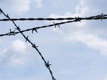Конец-вверх пересеченной колючей проволоки против пасмурного голубого неба - изолированного элемента дизайна стоковые фотографии rf
