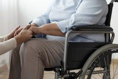 Конец-вверх персоны поддерживая парализовыванную старшую женщину в wh стоковое изображение rf