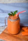 Конец-вверх питья smoothie моркови на голубой предпосылке ткани Здоровый напиток вытрезвителя в опарнике каменщика рядом с отрезк Стоковые Фото
