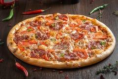 Конец-вверх пиццы Диабло на деревянном столе рядом с перцами и condiments стоковые фото