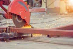 Конец вверх пламени искрится с механическим инструментом точильщика электрическим для резать стальную трубу в мастерской стоковое фото