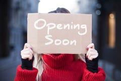 """Конец-вверх планшета картона с надписью """"скоро раскрывая """"в руках молодой женщины в красном свитере стоковое изображение"""
